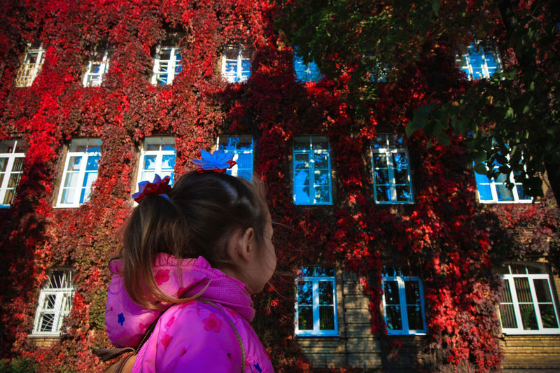 Low Angle View Of Girl Looking At Ivies On Building During Autumn