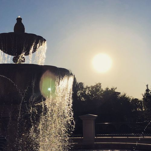 Low angle view of fountain against sky during sunset