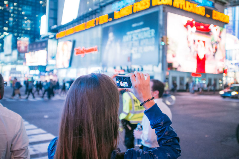 Rear view of woman photographing with mobile phone while standing against building at times square