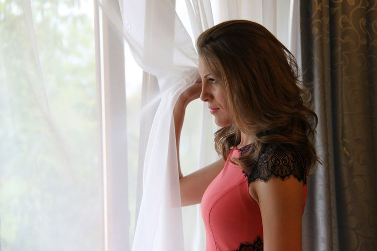 Side View Of Beautiful Woman Holding White Curtain By Window At Home