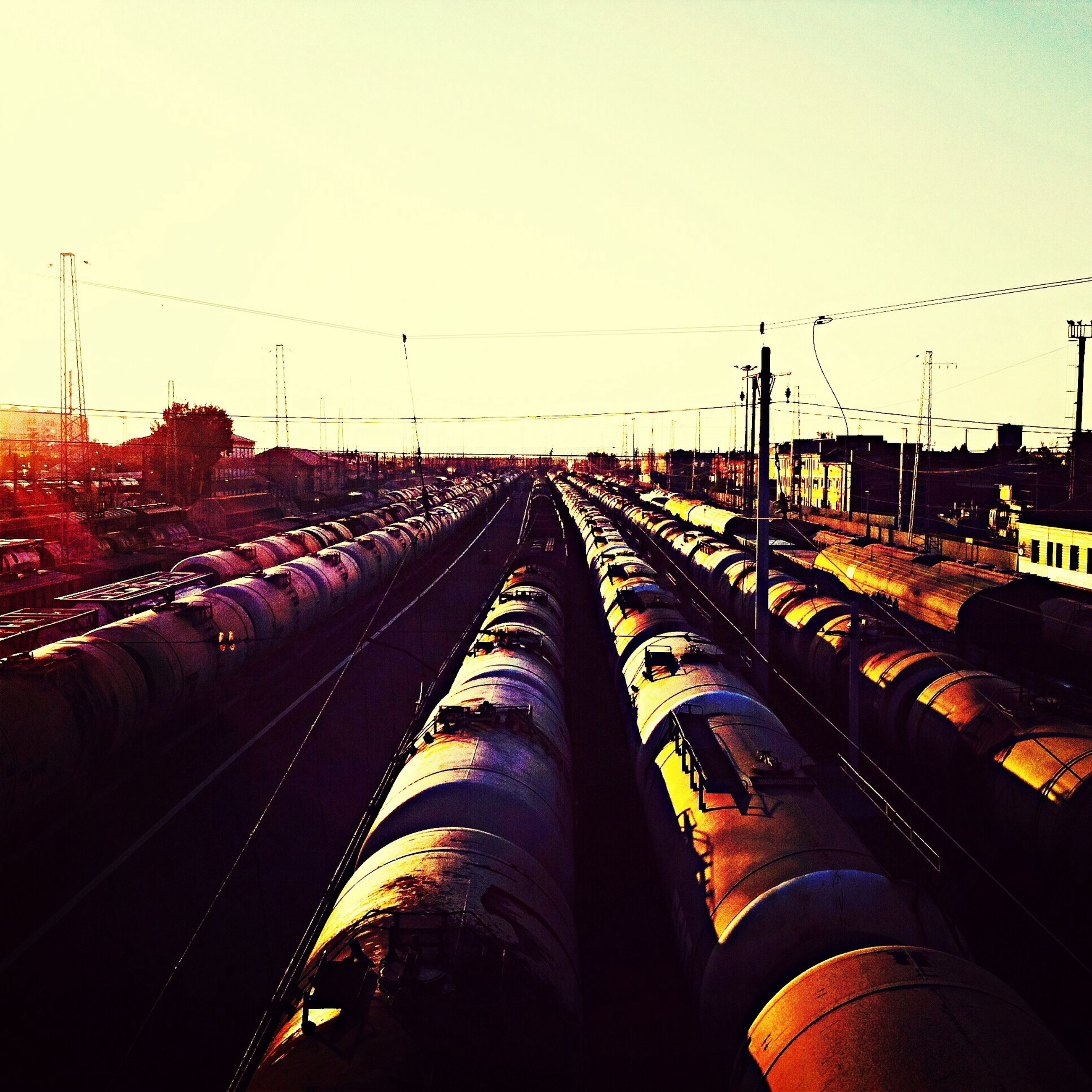 railroad track, transportation, clear sky, diminishing perspective, rail transportation, sky, built structure, high angle view, architecture, building exterior, the way forward, vanishing point, outdoors, illuminated, power line, dusk, connection, no people, copy space, in a row