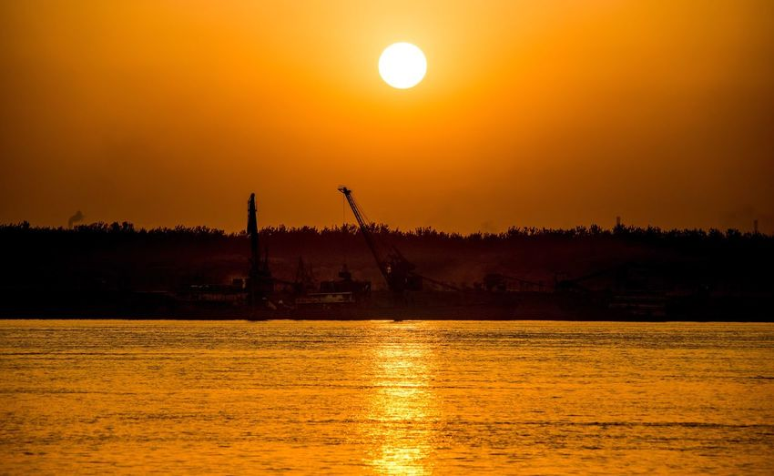setting sun Sunset Orange Color Sun Beauty In Nature Silhouette Scenics Water Tranquility Nature Tranquil Scene Reflection Sky No People Waterfront Outdoors Sea Sunlight Travel Destinations Tree