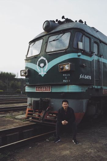 Train Transportation Mode Of Transportation One Person Real People Sitting Front View Young Adult Casual Clothing Looking At Camera Lifestyles Leisure Activity Portrait Railroad Track Track Rail Transportation