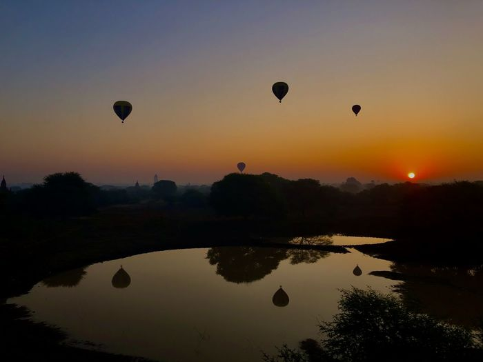 Silhouette hot air balloon flying against sky during sunset