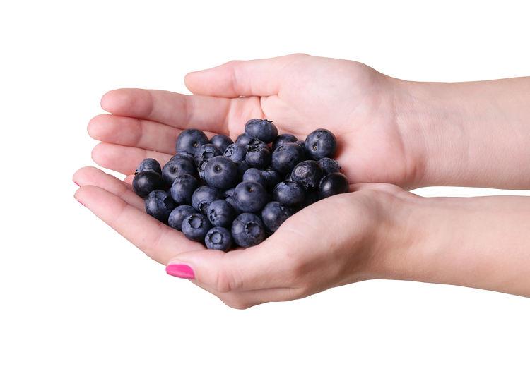 Cropped image of hand holding fruit against white background