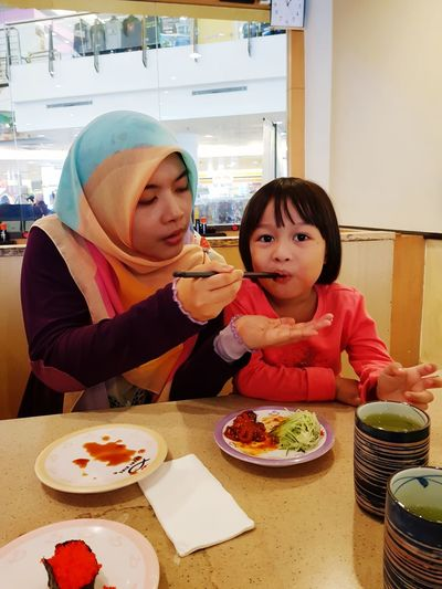 Mother Feeding Daughter At Table In Restaurant