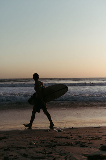Man with surfboard on beach against sky during sunset