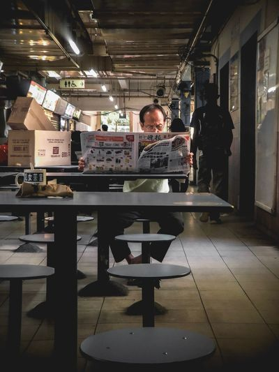 Man reading newspaper at market Market Street IPhone IPhone Photography Newspaper Relaxing Chiil Chinatown Street Photography Singapore Street Photography Minimal People Indoors  One Person Real People Men Sitting Lifestyles Front View Table The Street Photographer - 2018 EyeEm Awards EyeEmNewHere