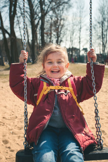 Portrait of smiling girl playing on swing at playground