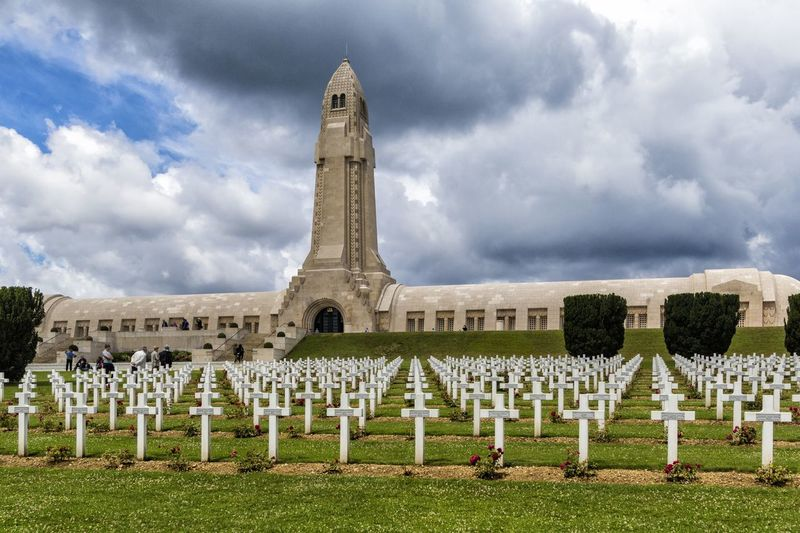 """The Douaumont ossuary (French: L'ossuaire de Douaumont) is a memorial containing the skeletal remains of soldiers who died on the battlefield during the Battle of Verdun in World War I. It is located in Douaumont, France, within the Verdun battlefield. It was built on the initiative of Charles Ginisty, Bishop of Verdun. It has been designated a """"nécropole nationale"""", or """"national cemetery"""" Battle Of Verdun Douaumont Ossuary L'ossuaire De Douaumont Ossuary Architecture Cemetery Cloud - Sky Cross Day Grass History History Place Memorial Monument Necropolis No People Outdoors Religion Sadness Sky Spirituality Tombstone World War 1 World War 1 Memorial"""