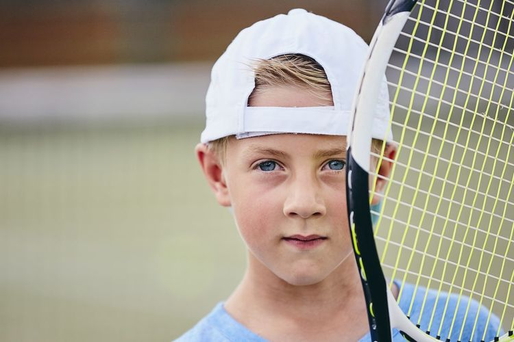 Close-Up Portrait Of Cute Boy With Tennis Racket At Court