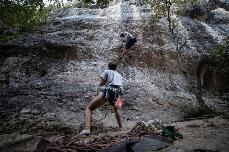 Rear view of men climbing rock