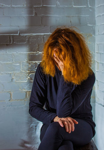 a woman is sitting desperately in front of a wall One Person Real People Wall Sitting Adult Hair Women Redhead Depression Sad Unhappy Religion Abuse Shadow Cross Desperate Caught Dependent Lonely Alone Abandoned Cellar