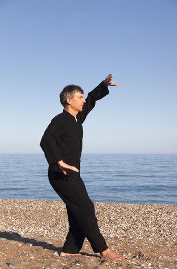 Man with arms raised on beach against clear sky