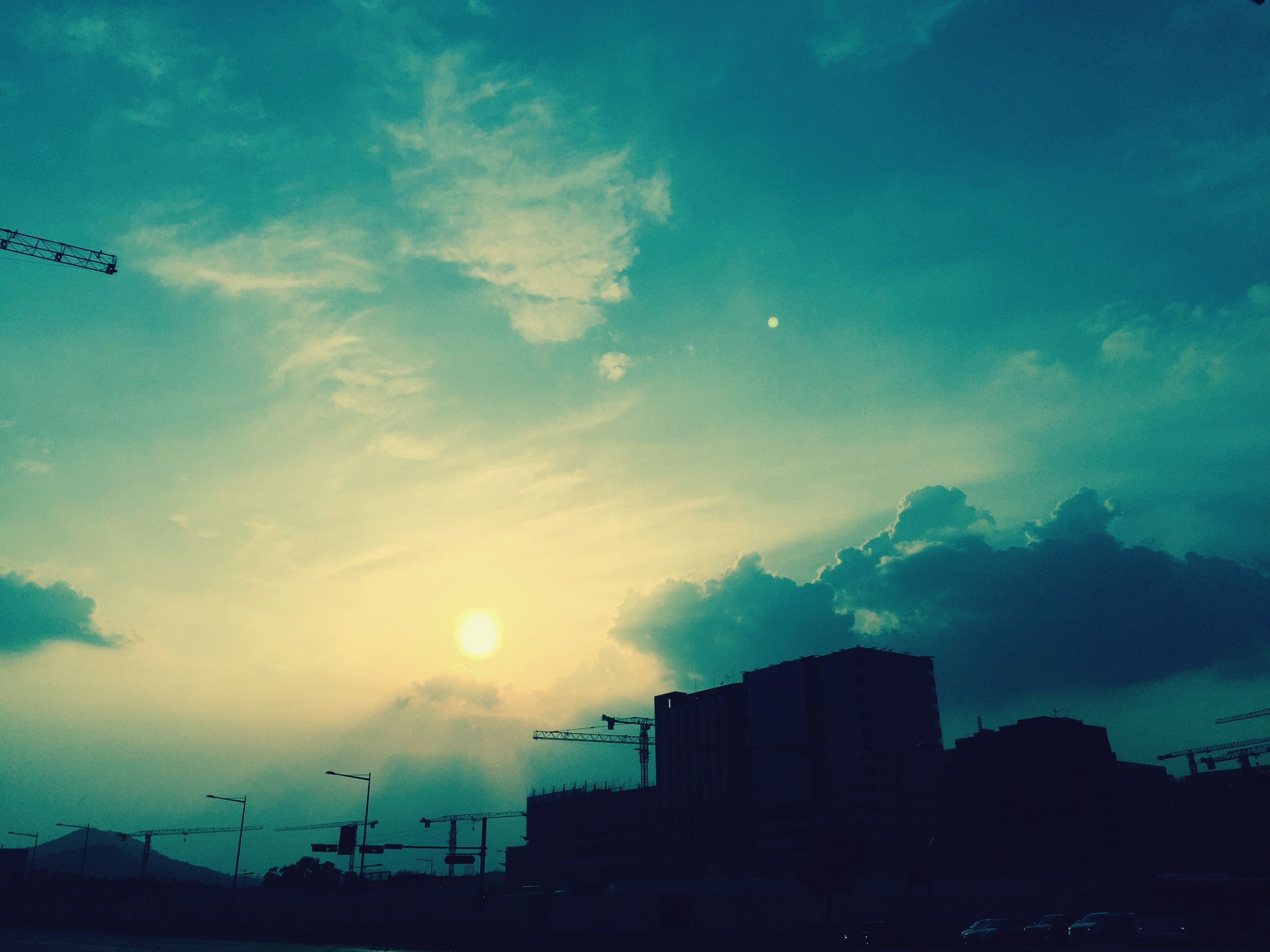 building exterior, architecture, built structure, sky, silhouette, sunset, cloud - sky, sun, city, low angle view, cloud, sunlight, building, blue, dusk, outdoors, nature, residential building, sunbeam, no people