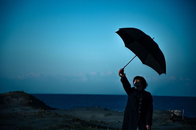 Woman holding umbrella while standing at beach against blue sky