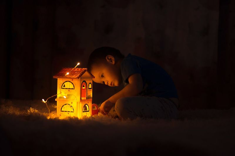 Boy Playing With Illuminated Model Home In Darkroom