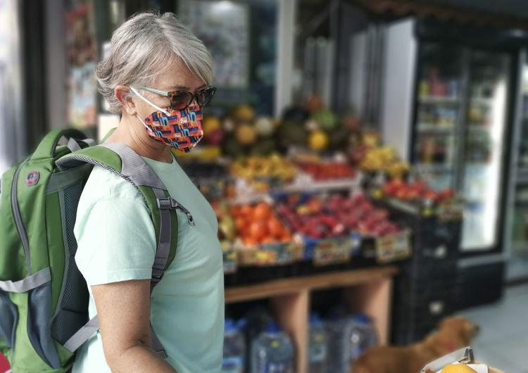 Senior woman wearing mask standing at supermarket
