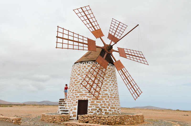 Woman standing on traditional windmill against sky