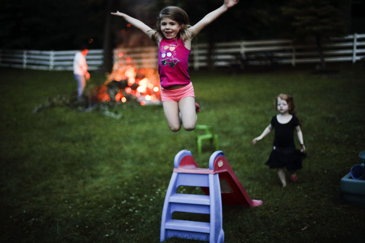 A young girl jumps off a slide while her sister watches with a campfire in the background. Campfire Child Childhood Elementary Age Enjoyment Focus On Foreground Full Length Fun Girls Grass Leisure Activity Lifestyles Night Outdoors People Playground Playing Real People Slide Togetherness EyeEm Selects Sommergefühle