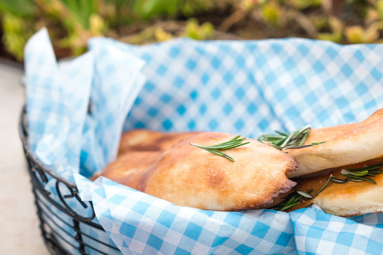 Close-up of ciabatta bread with rosemary in basket