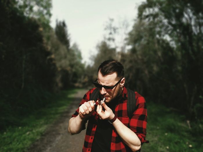 Young man burning smoking pipe in forest