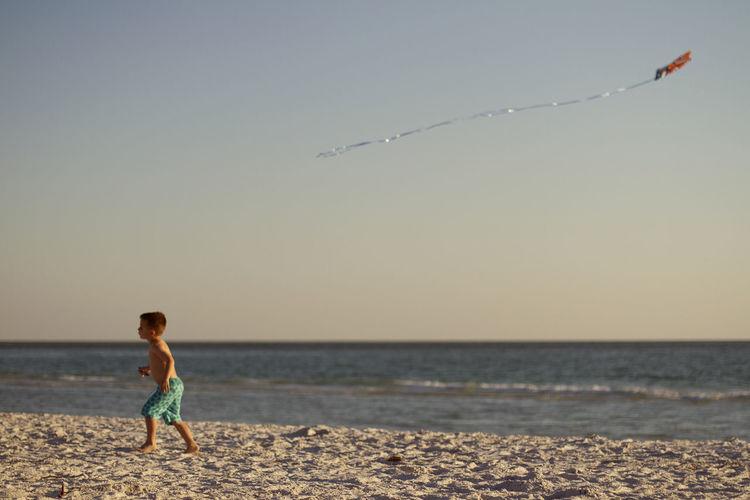 Boy running on sand at beach against sky