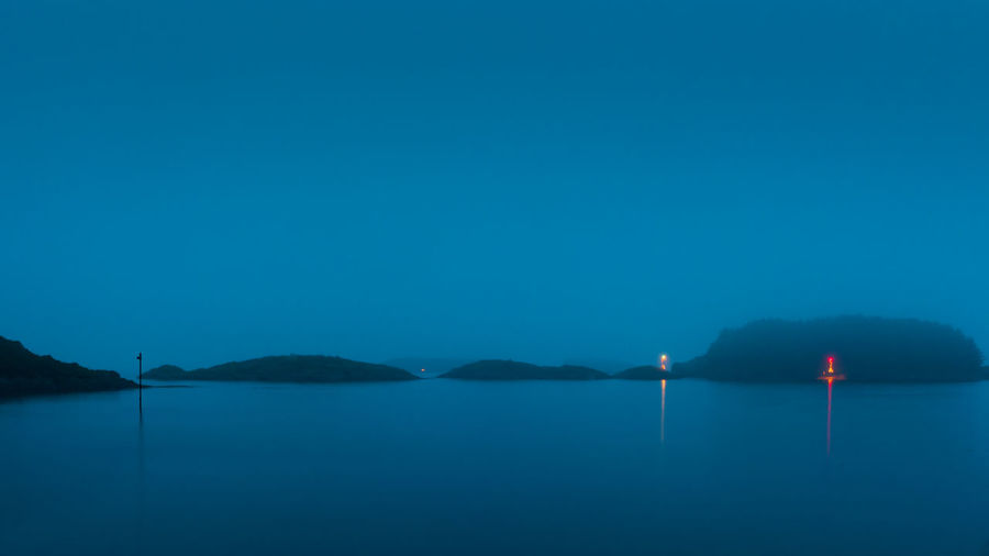 Coast landscape with lighthouses in misty evening. Water Scenics - Nature Tranquil Scene Beauty In Nature Tranquility Blue No People Waterfront Non-urban Scene Reflection Outdoors Lighthouse Navigation Mark Seascape Seamark Islands Coastscape Norway Karmøy Scandinavia Nordic Night Nightphotography Evening