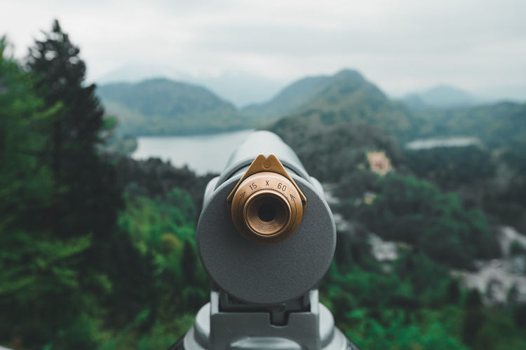 Close-up of coin-operated binoculars against sky and mountains