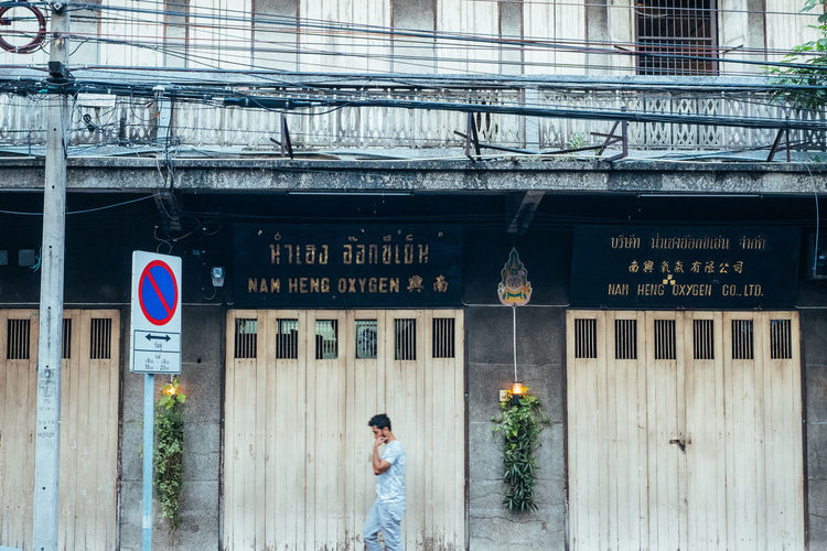 Architecture Building Exterior Built Structure One Person Text Day Real People Entrance Western Script Communication Standing Sign Men City Door Building Adult Rear View Lifestyles