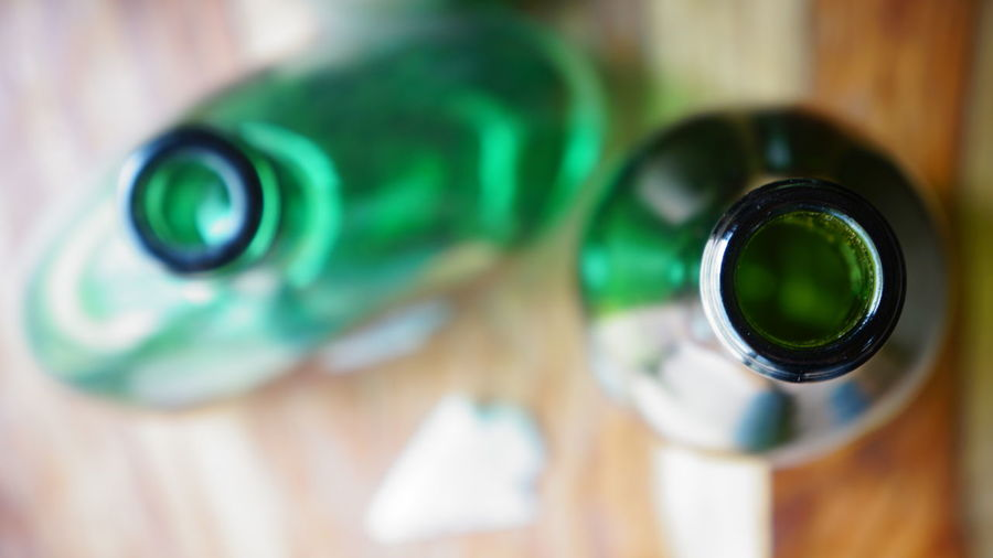 High angle view and shallow depth of field with focus on lip of one of two green bottles on a wooden background with an arrowhead placed near them. A Bird's Eye View Arrowhead Backgrounds Bottle Circle Close-up Depth Of Field Focus On Foreground Full Frame Green High Angle View Macro Refreshment Selective Focus Shiny Still Life Wine Bottle Wooden