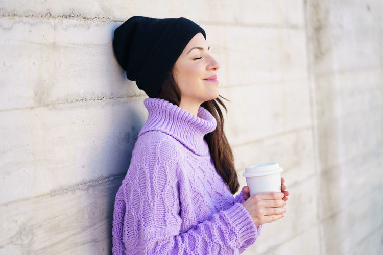 Young woman drinking coffee cup on wall