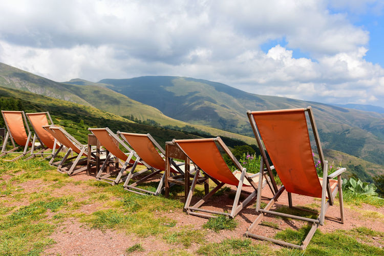 Deck chairs on field by mountains against sky