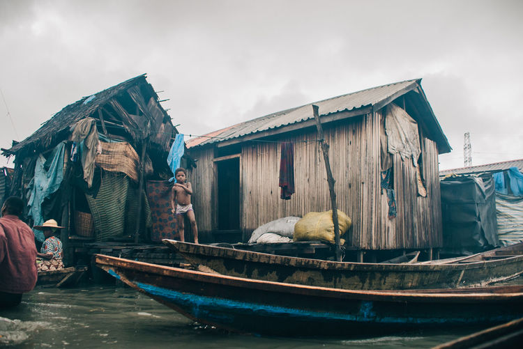Makoko Slum Animal Architecture Building Exterior Built Structure Cloud - Sky Day Domestic Fishing Industry Mammal Mode Of Transportation Nature Nautical Vessel No People One Animal Outdoors Pets Sky Transportation Vertebrate Water