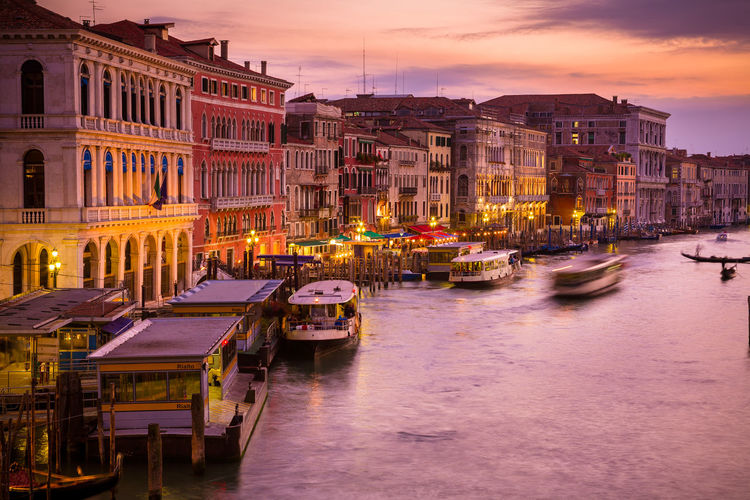 Boats on grand canal during sunset in city