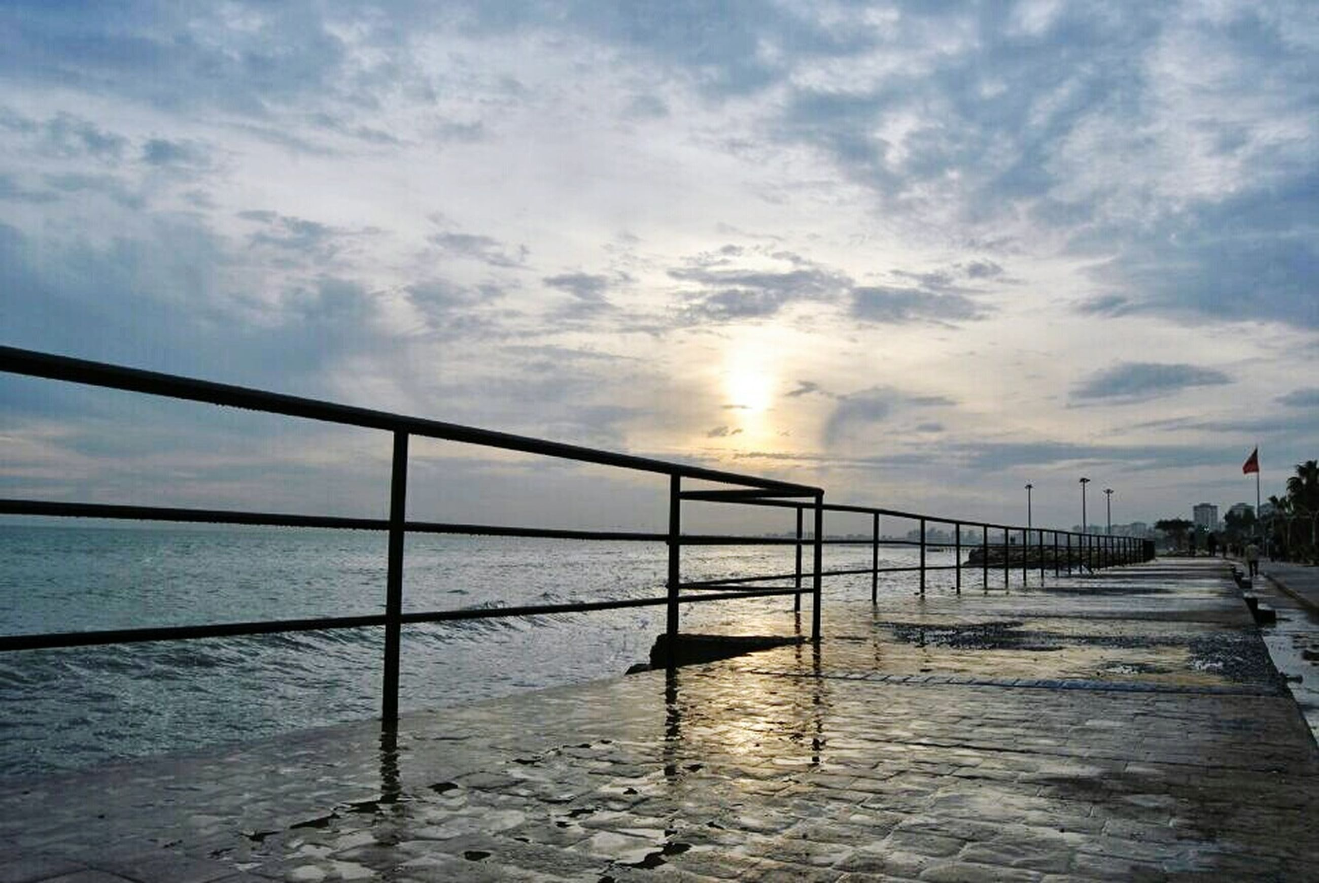 sky, water, cloud - sky, railing, sea, pier, tranquility, sunset, cloudy, scenics, sun, tranquil scene, nature, built structure, sunlight, beauty in nature, horizon over water, cloud, reflection, sunbeam