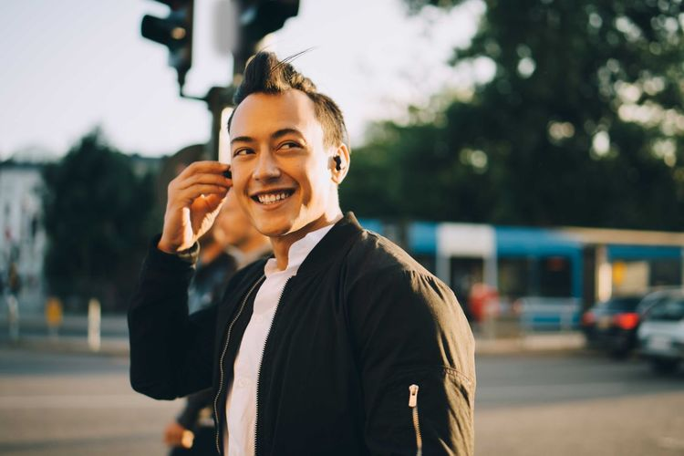 Portrait of smiling man using mobile phone in city