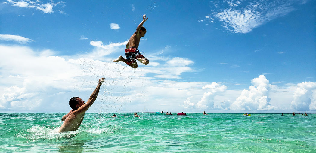 Father throwing son in mid-air while swimming in sea