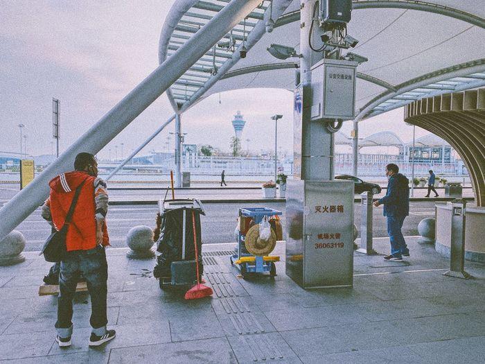 Rear view of people walking on bridge in city