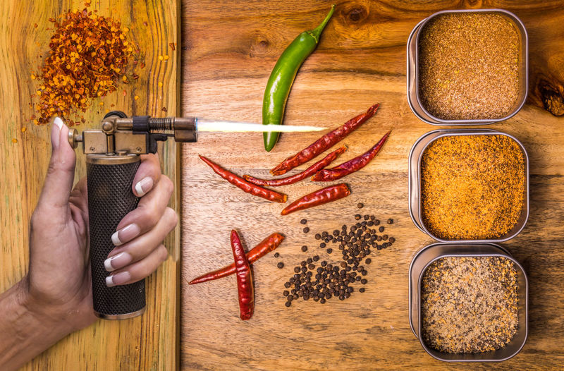 Hot stuff Burning Hot Chilli Pepper Directly Above Finger Fire Food Food And Drink Freshness Hand Healthy Eating High Angle View Holding Hot Spices Human Body Part Human Hand Ingredient Jalapeños One Person Preparation  Spice Table Vegetable Wellbeing Wood - Material