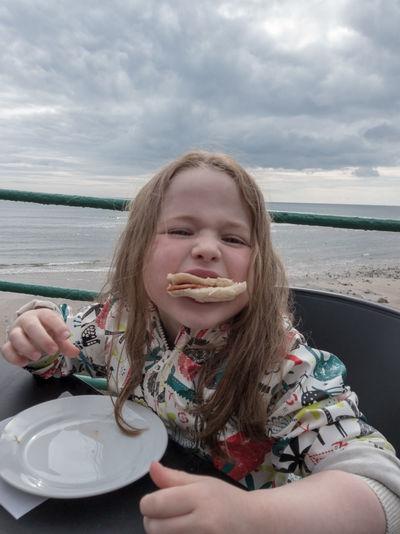 Portrait Of Girl Eating Food Against Sky
