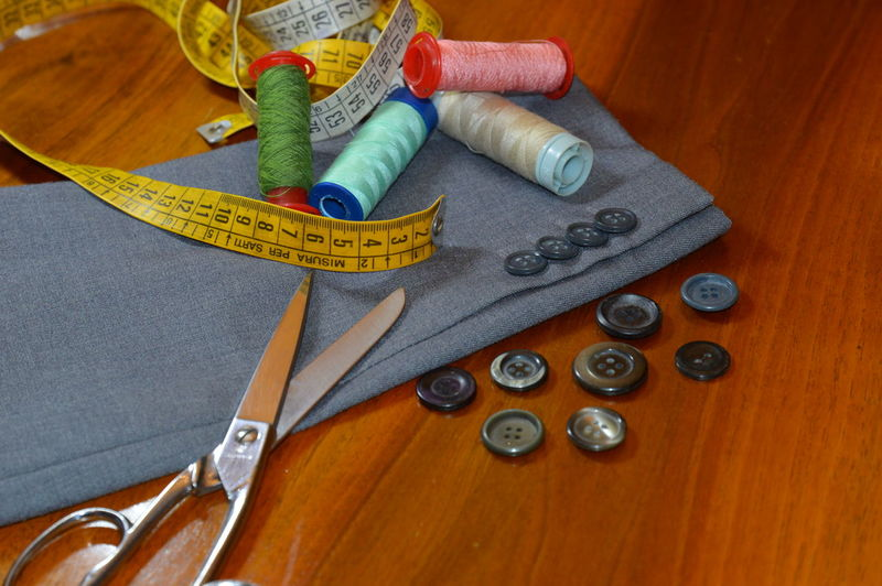 High angle view of sewing items with fabric on wooden table