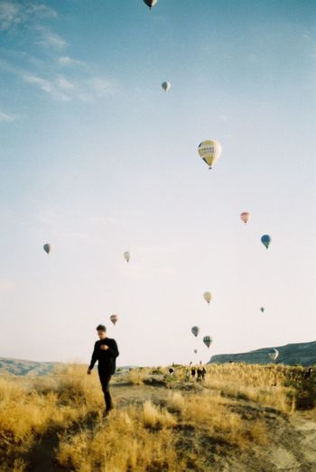People On Mountain Against Hot Air Balloons Flying In Sky