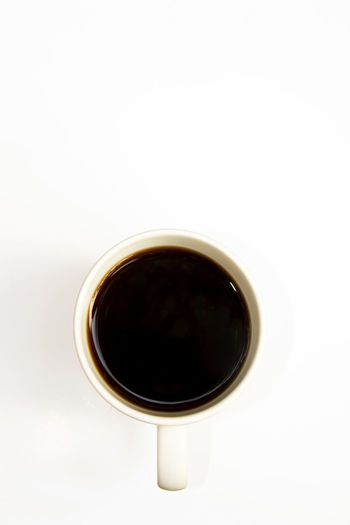 High angle view of black coffee against white background