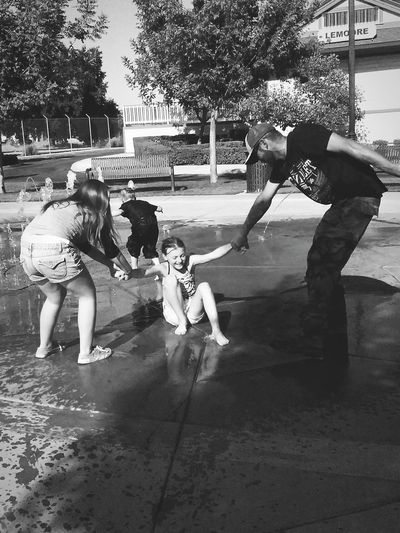 Fatherhood Moments Helping Hands Luaghing Out Loud Family Children Playing Moments That Count Simple Things Outside Being Productive & Boys Playing Siblings Summer Sunny Day Grass Water Fountains Park Tree In Town Hanging Out Brother & Sister Falling Down Smiling Teamwork