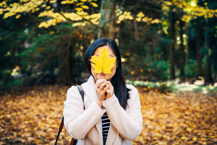 Woman Hiding Face With Dry Yellow Leaf Against Trees In Forest During Autumn