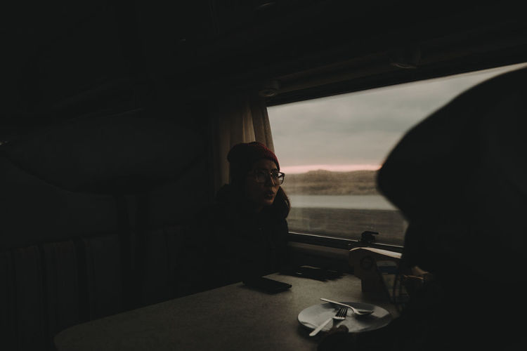 Woman traveling in train during sunset