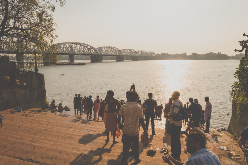 People on bridge over river against clear sky