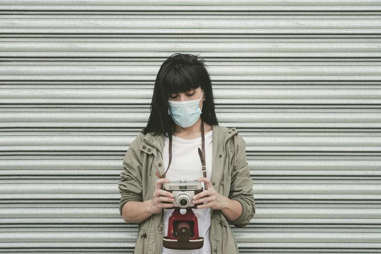 Portrait of senior woman standing against closed shutter