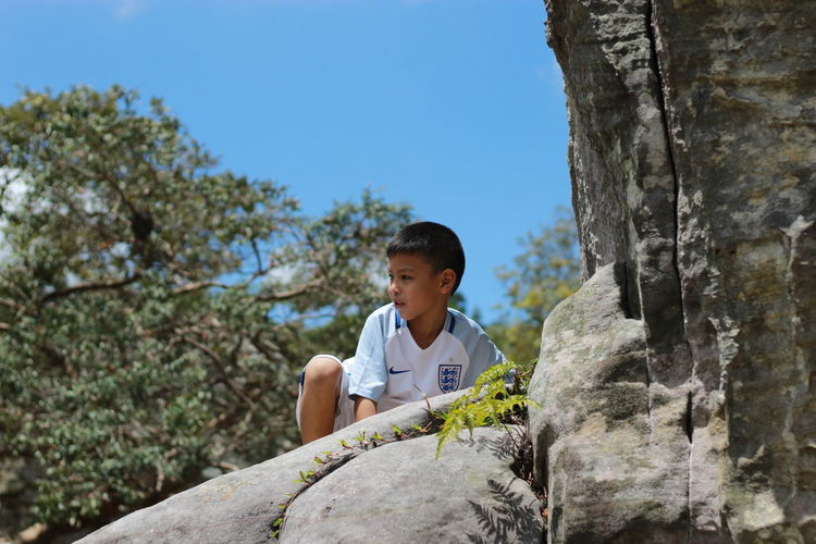 Boy standing on rock against sky